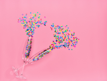 Two champagne glasses with colorful confetti  on pink background. Top view Banco de Imagens