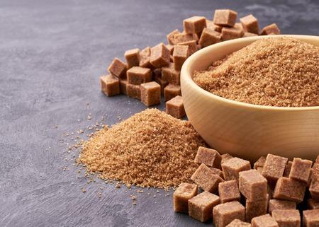 Brown sugar in wooden bowl, Brown sugar  in background. Sugar cubes Banco de Imagens