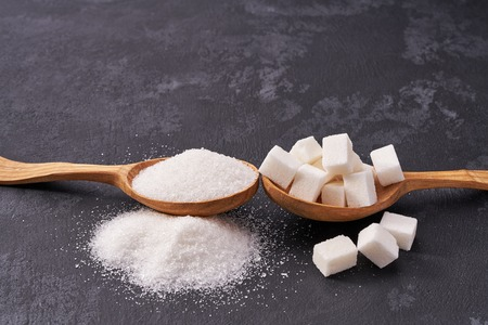 White sugar cubes  and granulated sugar  in two spoons with white sugar on  black table.Flat lay Banco de Imagens