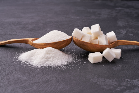 White sugar cubes  and granulated sugar  in two spoons with white sugar on  black table.