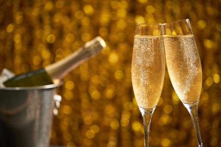 Two glasses of champagne with lights in the background., very shallow depth of fiel Imagens