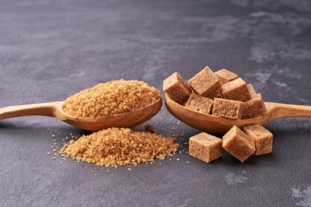 Brown sugar cubes  and granulated sugar  in two spoons with white sugar on  black table.Top view .Raw organic cane sugar