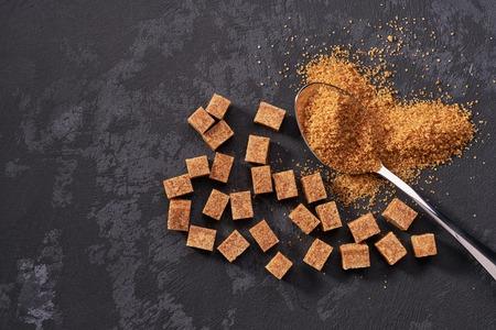 Granulated brown  sugar in metal spoon and sugar pile.Top view Raw organic cane sugar
