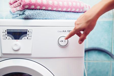 lavando ropa: La lavadora que cuesta en un cuarto de baño. La mujer opera la máquina lavadora Foto de archivo