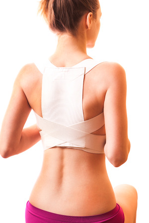 corrective: The girl in the corrector for the spine on a white background.