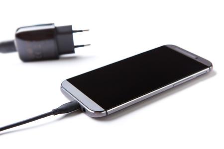 Handy und Ladegerät sind auf dem Tisch.