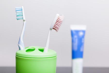 Zwei Zahnbürsten und Zahnpasta stehen auf einem Tisch in einem Glas.