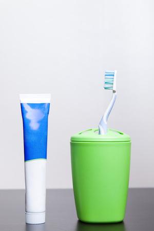 Zahnbürsten und Zahnpasta stehen auf einem Tisch in einem Glas.