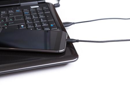 Telefon liegend auf einem Laptop auf einem weißen Hintergrund