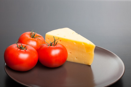 Piece of cheese and tomatoes lying on the plate.