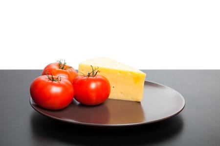 Stück Käse und Tomaten auf der Platte liegen.