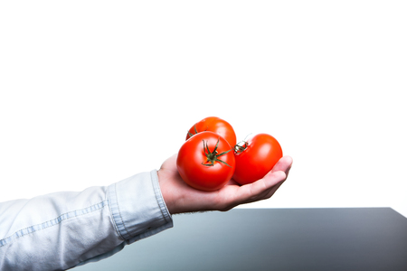 only 3 people: A man holding a tomato, vegetarian food.