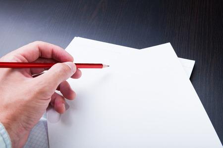 Man macht sich Notizen in Bleistift auf Papier.