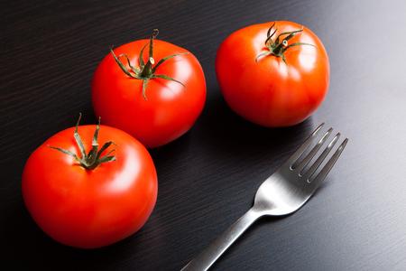 Drei rote reife Tomaten und Gabel auf dem Tisch.