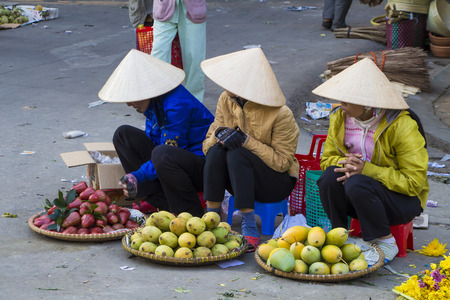 Vietnamese vendors selling fruit and vegetables at Dalat city market, Vietnam Banco de Imagens
