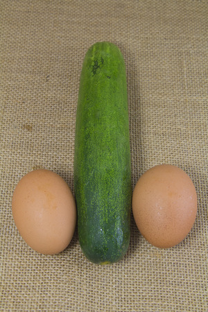 parody: cucumber and egg look like penis on sack Stock Photo