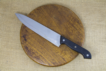 wooden block: Knife on wooden block with sack background Stock Photo