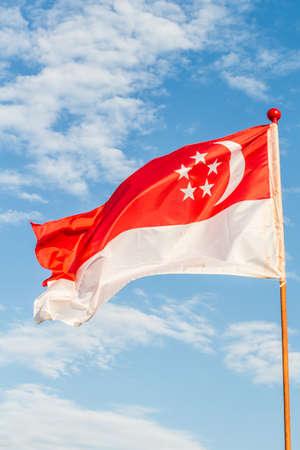 singaporean flag: singapore flag in blue sky