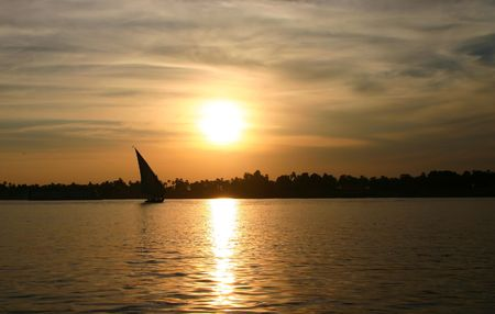 Felucca sailing on the River Nile against sunset. Stock Photo