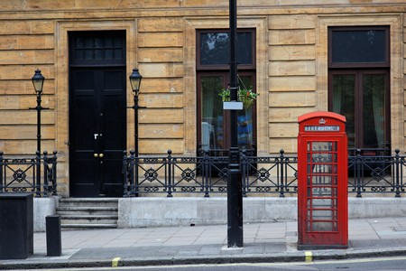 Red phone booths on street of central London. UK.