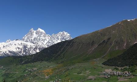 Double peaks of Mt. Ushba and Mulakhi Village. Svaneti. Georgia. Stock Photo - 9059799