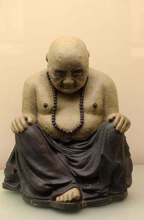 bowed: Sitting bowed Buddha. Antique sculpture. Hong kong.