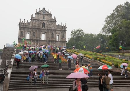 People under colourful umbrellas in front of ruined church of St Paul. Macau. China