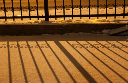Shadow of fence on snow in orange street light at night. Russia. photo