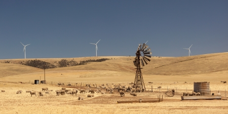 Old broken wind pump and new wind generators distorted by hot air  South Australia  photo