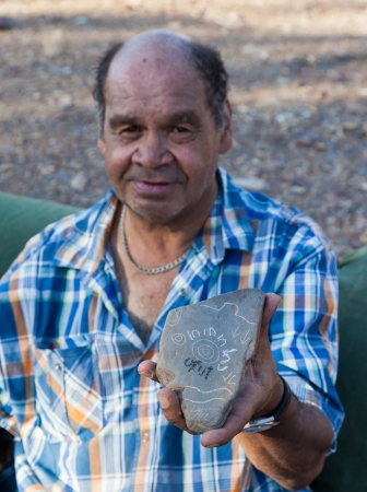 A man holds stone with aboriginal drawings  Flinders Ranges  South Australia