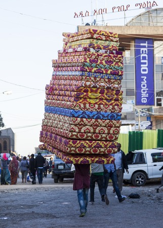ababa: Man carries pile of foam mattresses in Merkato market  Addis Ababa  Ethiopia