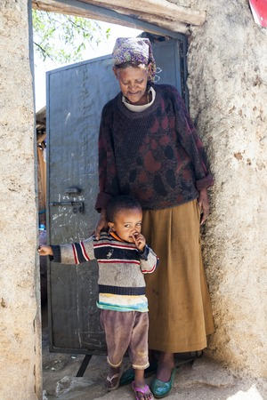 HARAR, ETHIOPIA - DECEMBER 24, 2013  Unidentified grandmother with grandchild posing in the entrance of their house in ancient walled city of Jugol, that daily life is almost unchanged in more than four hundred years