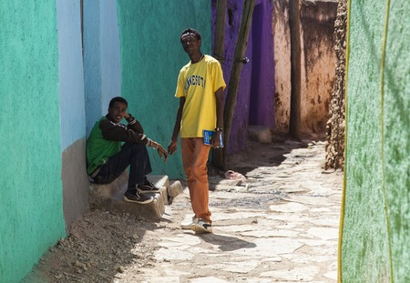 HARAR, ETHIOPIA - DECEMBER 24, 2013  Two unidentified young men posing in typical surroundings in ancient walled city of Jugol, that daily life is almost unchanged in more than four hundred years