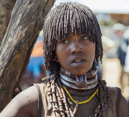 TURMI, OMO VALLEY, ETHIOPIA - DECEMBER 30, 2013: Unidentified Hamar woman seller at village market. Weekly markets are important events in Omo Valley tribal life.