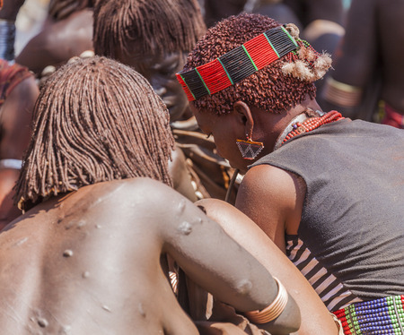 bracelet tattoo: TURMI, OMO VALLEY, ETHIOPIA - DECEMBER 30, 2013: Unidentified Hamar women at village market. Weekly markets are important events in Omo Valley tribal life.