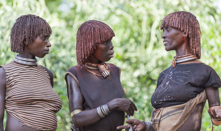 manhood: TURMI, OMO VALLEY, ETHIOPIA - DECEMBER 30, 2013: Unidentified women get ready for dancing at bull jumping ceremony. Jumping of the bull is a rite of passage into manhood in some Omo Valley tribes.