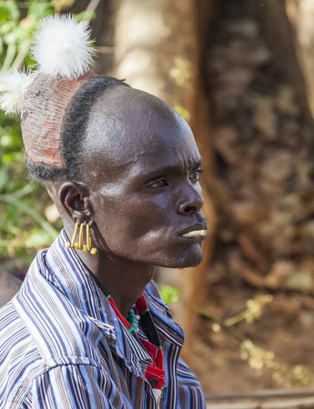 manhood: TURMI, OMO VALLEY, ETHIOPIA - DECEMBER 30, 2013: Unidentified traditionally dressed Hamar man with chewing stick in his mouth at a bull jumping ceremony. Jumping of the bull is a rite of passage into manhood in some Omo Valley tribes. Editorial