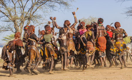 TURMI, OMO VALLEY, ETHIOPIA - DECEMBER 30, 2013: Unidentified group of Hamar women dance at bull jumping ceremony. Jumping of the bull is a rite of passage into manhood in some Omo Valley tribes. Sajtókép