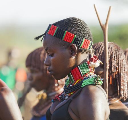 tribu: TURMI, Valle del Omo, ETIOPÍA - 30 de diciembre 2013: Retrato de la mujer joven no identificado en Hamar ceremonia del salto del toro. Ceremonia Bull Jumping es un rito de paso a la edad adulta en algunas tribus del valle del Omo.