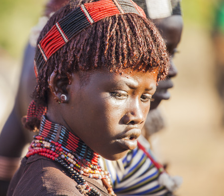 TURMI, OMO VALLEY, ETHIOPIA - DECEMBER 30, 2013: Portrait of unidentified young Hamar woman at bull jumping ceremony. Bull Jumping ceremony is a rite of passage into manhood in some Omo Valley tribes. Stock Photo - 32477411