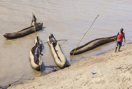 poling: OMORATO, LOWER OMO VALLEY, ETHIOPIA - JANUARY 31, 2012: Traditional dassanech boats on the Omo river. Dugout boats are made from a hollowed tree trunk.