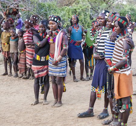 gearing: TURMI, OMO VALLEY, ETHIOPIA - DECEMBER 30, 2013: Unidentified young boys and girls gearing at the traditional evangaty (night dance) ceremony.