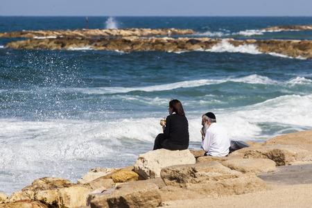 kippah: TEL AVIV, ISRAEL - OCTOBER 19, 2014: Unidentified local couple at the seashore enjoys the view.