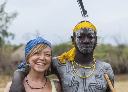 MAGO NATIONAL PARK OMO VALLEY ETHIOPIA  JANUARY 01 2014: Unidentified European woman and man from Mursi tribe in Mirobey village.