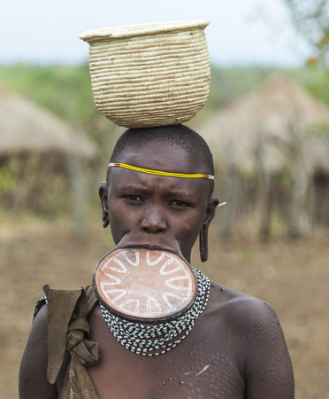 native culture: MAGO NATIONAL PARK OMO VALLEY ETHIOPIA  JANUARY 01 2014: Unidentified Woman from Mursi tribe in Mirobey village. Mursi woman are famous for their traditional lip plate Editorial