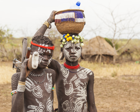 african basket: MAGO NATIONAL PARK OMO VALLEY ETHIOPIA  JANUARY 01 2014: Unidentified boys from Mursi tribe with machine gun in Mirobey village.