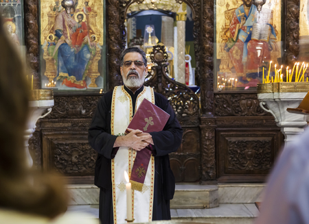 sotana: NAZARET. ISRAEL - 25 de octubre 2014: el bautismo infantil en la Basílica ortodoxa griega de la Anunciación. Editorial