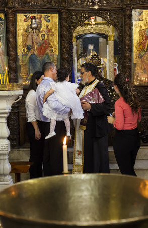 baptizing: NAZARETH. ISRAEL - OCTOBER 25, 2014: Child baptism in Greek Orthodox Basilica of the Annunciation. Editorial