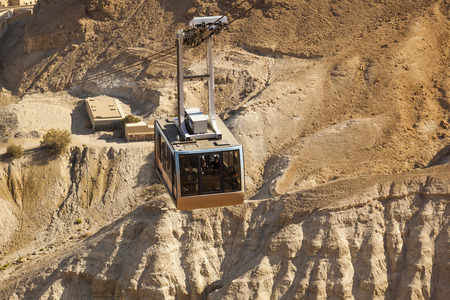 masada: ISRAEL, MASADA - OCTOBER 27, 2014: Cable car to ruins of Masada ancient fortress - one of the most visited place in places in country.
