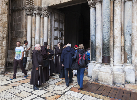 JRUSALEM OLD TOWN, ISRAEL - OCTOBER 31, 2014: Unidentified people and Fathers from Franciscan Order on traditional Friday Via Dolorosa way of sorrows procession at the entrance of Church of the Holy Sepulchre